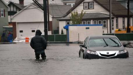 A man passes a submerged vehicle at the
