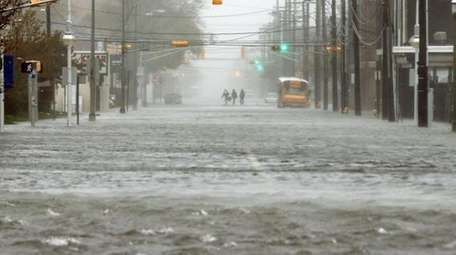 People walk down a flooded street as Hurricane