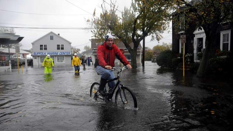 A man rides his bicycle through Prospect Street