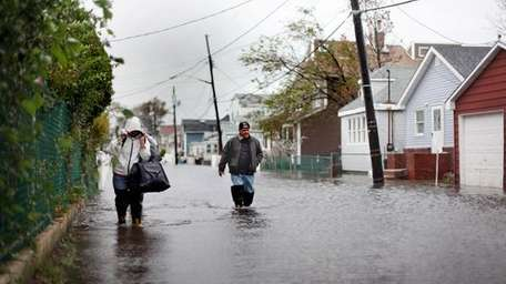 People wade through flood water in Broad Channel
