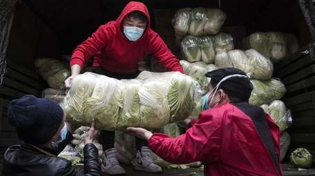 Employees wear protective masks Monday while carrying vegetables