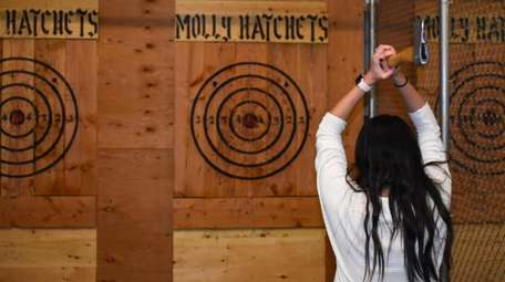 Kirstin Montgomery, of Centereach, tries at ax throwing