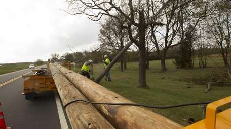 Verizon linemen prep to replace downed poles on