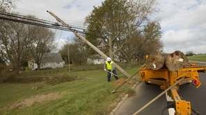 A Verizon lineman prepares to replace downed poles