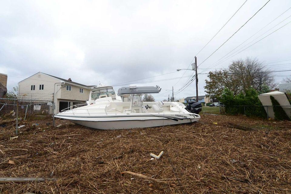 A boat lies on debris in Long Beach