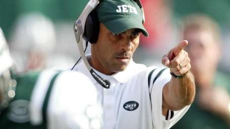 Herm Edwards directs a play from the sidelines