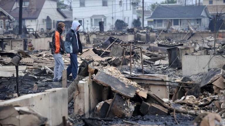Two boys view damage in a neighborhood in