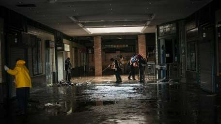 Workers clean up the Stillwell Avenue subway station
