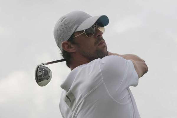 Olympic swimming gold medalist Michael Phelps tees off