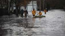 Firefighters walk through flooding at Main Street and