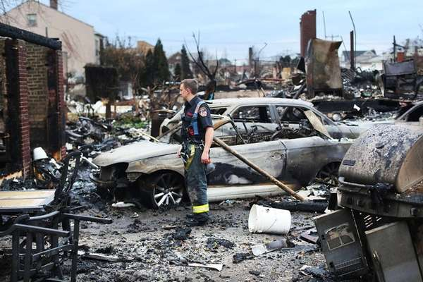 A firefighter stands among the remains of homes