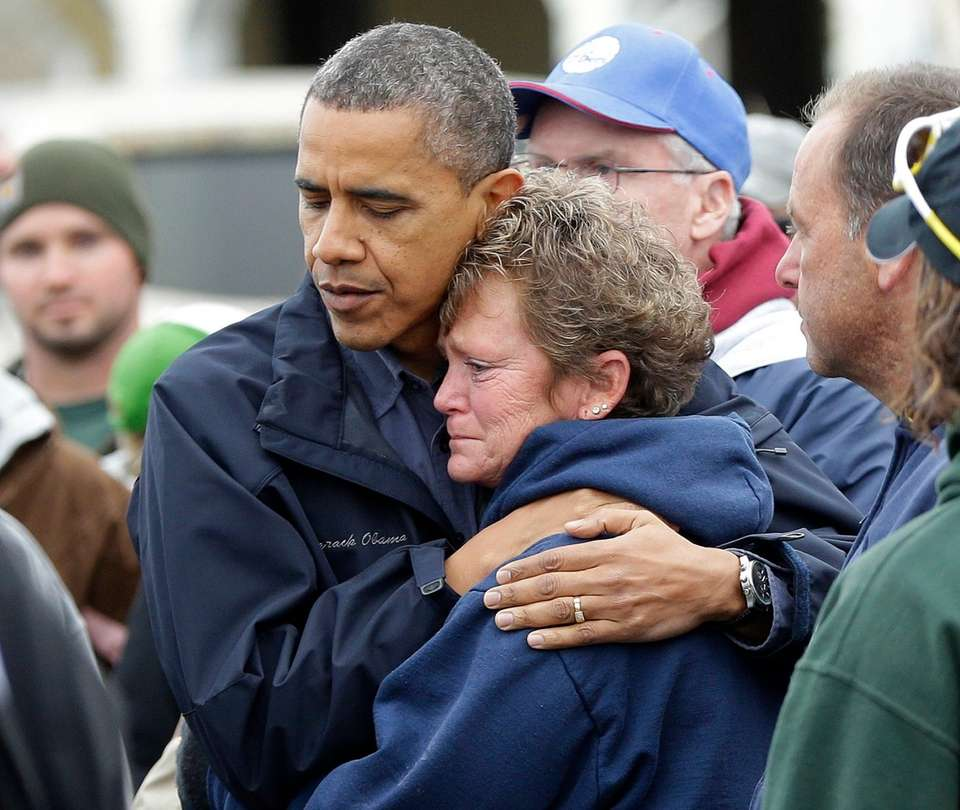 President Barack Obama, left, embraces Donna Vanzant, right,