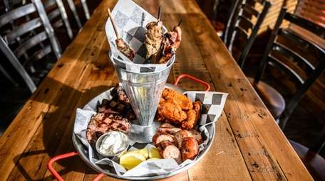 """Holy Smoke's """"combo feast"""" features wings, pork skewers,"""