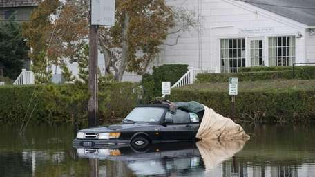 A car submerged in floodwaters, in the parking