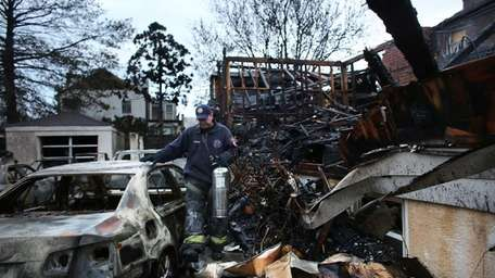 Firefighters walk among the remains of homes burned