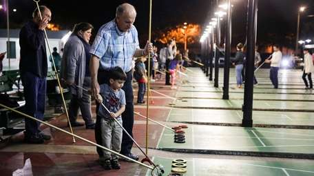 Lou Pekrul plays shuffleboard with his grandson William,