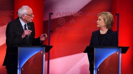 Democratic presidential candidate Hillary Clinton listens as Bernie