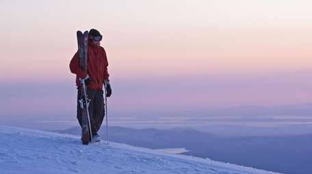 A skiier greets the dawn from the summit