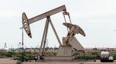 An oil pump jack operates near U.S. Route
