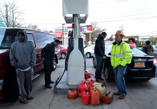 People wait to get gasoline cans filled at