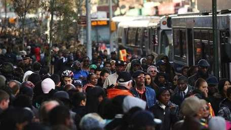 Thousands of people wait to board city buses
