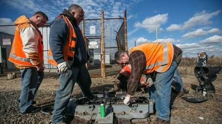 Workers repair storm damage at the LIRR's Long