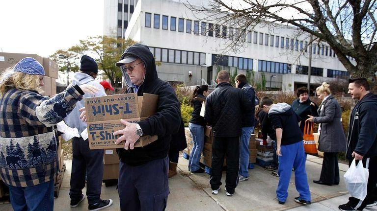 Red Cross volunteers distribute food packages in front