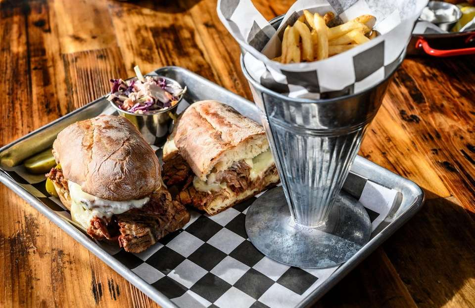 The brisket sandwich, blanketed with mozzarella, is served
