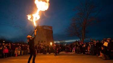 A juggler performs a fire stunt in front
