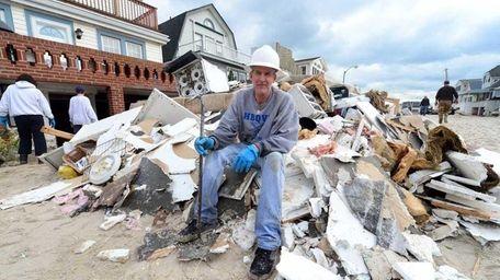 John Joyce sits on a pile of garbage