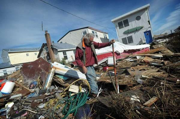 Greg Snow attempts to clear debris from superstorm
