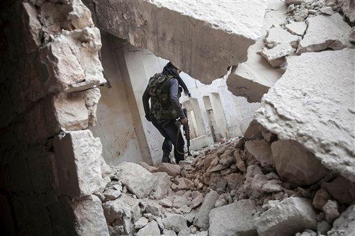 A rebel fighter walks among the debris of