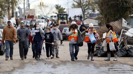 Volunteers walk toward homes to help residents clean