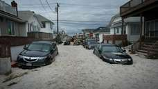 Cars are partly submerged with sand outside a