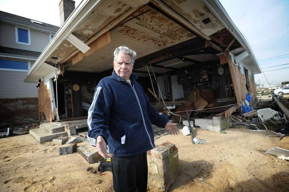 Joseph Bivona surveys the damage to his home