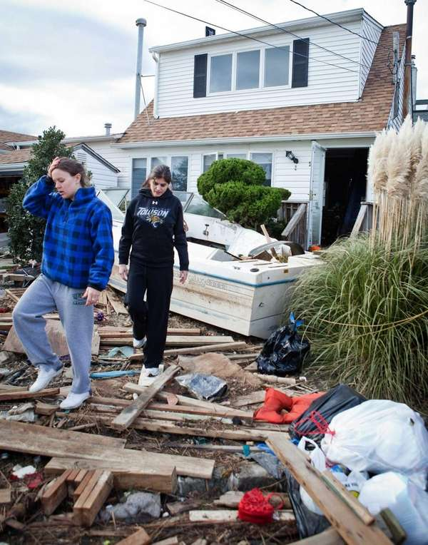 Jackie Dougherty, left, leaves her home in Lindenhurst