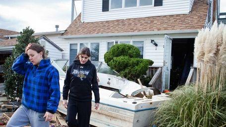 Jackie Dougherty, left, leaves her home in Lindenhurst