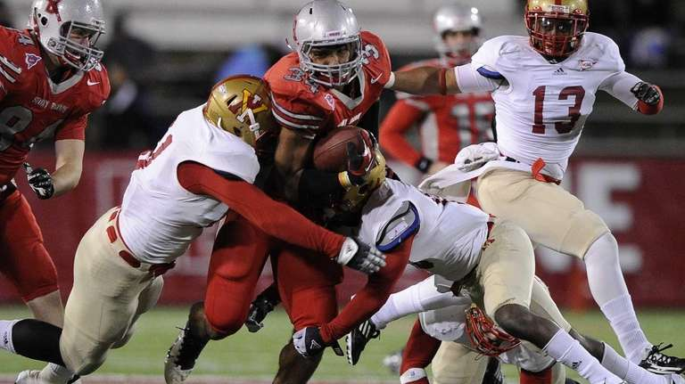 Stony Brook's Marcus Coker is tackled by Virginia