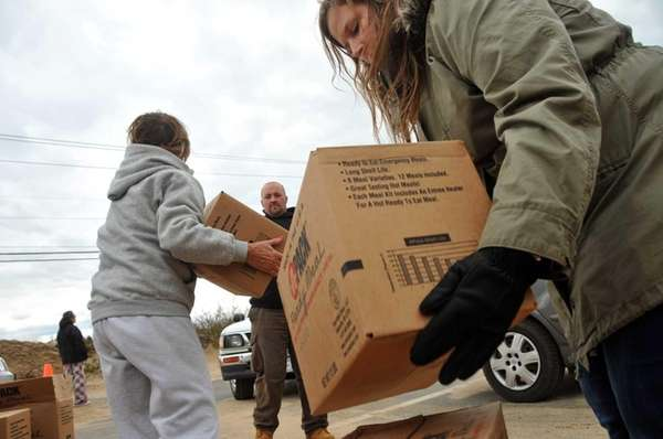 Volunteers distribute self-heating meals provided by FEMA to