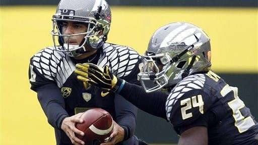 Oregon quarterback Marcus Mariota, left, hands off to
