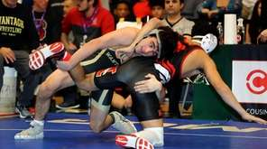 Wantagh's Ben Rogers controls Mineola's Mathias Silva with