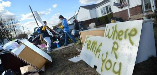 People clean up debris from a destroyed home