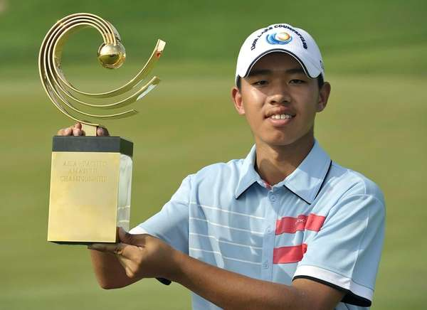 Guan Tianlang of China poses with the winner's