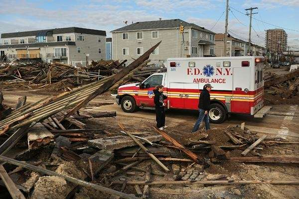 People walk through the heavily damaged Far Rockaway
