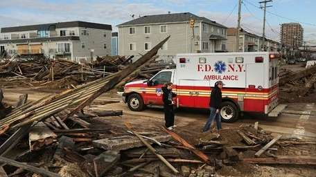 People walk through the heavily damaged Far Rockaway