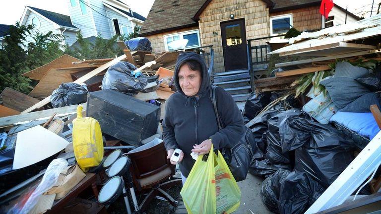 Josephine Montgomery walks through mountains of debris piled
