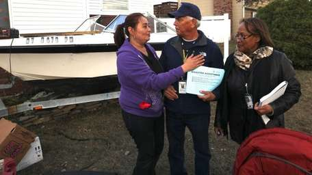 Sally Walker, left, embraces FEMA representatives when they