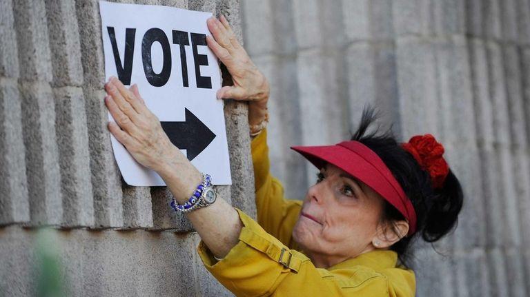 Election worker Susan Keller sets up directional signs