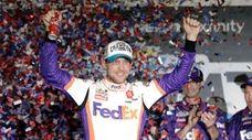 Denny Hamlin celebrates in Victory Lane after winning