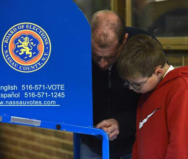 Paul Bernieri casts his vote as his son